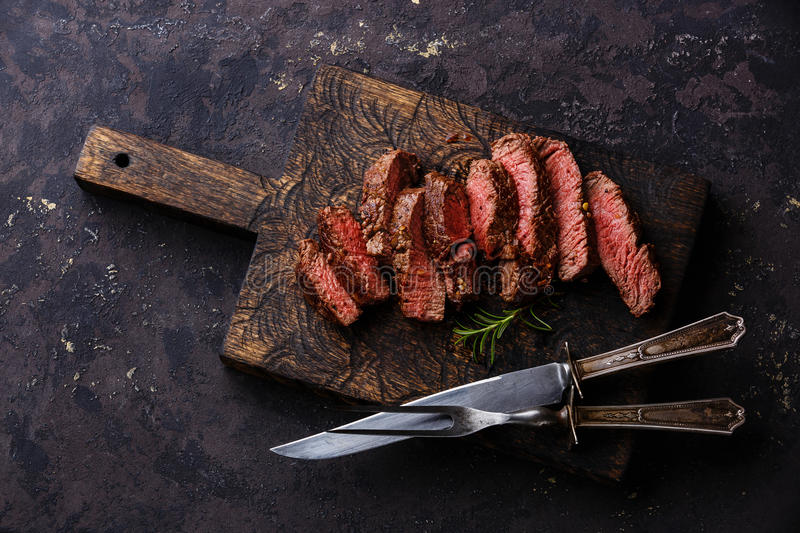 Sliced grilled Beef steak with knife and fork royalty free stock photos