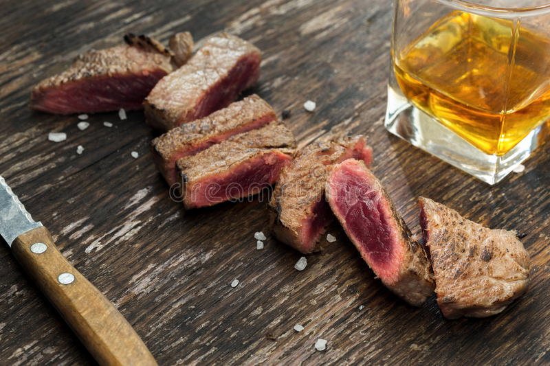 Sliced grilled beef steak on wooden table with whiskey. Close up royalty free stock images