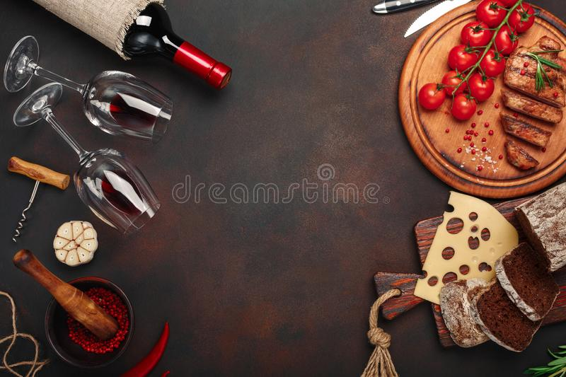 Sliced grilled pork steaks on a cutting board with cherry tomatoes, cheese, bread, garlic and rosemary, bottle of wine, wine glass stock photography