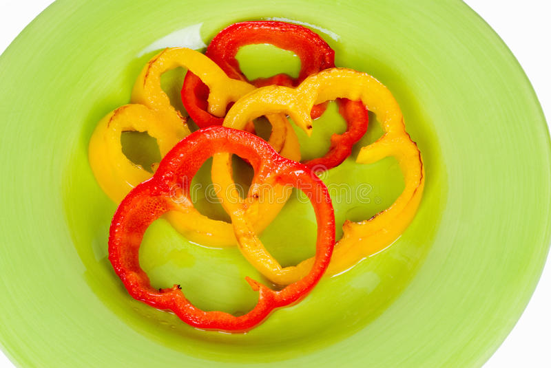 Sliced Grilled Red and Yellow Bell Peppers. Slices of grilled red and yellow bell peppers served on a lime green plate stock photo
