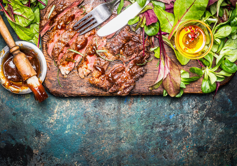 Sliced grilled steak served with green salad, Barbecue sauce and cutlery on wooden gutting board and rustic background, top view. Border stock photos