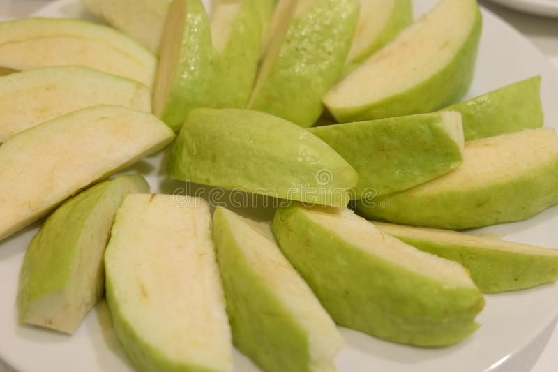 Sliced guava arranged in white dish plate stock photos