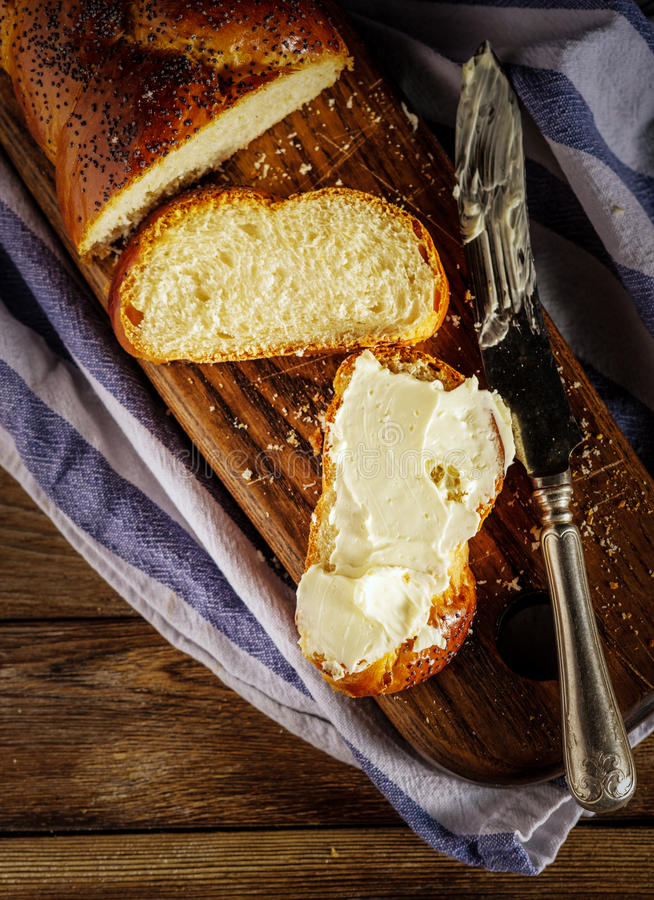 Sliced Hala with butter is a traditional jewish sweet fresh sabbath bread loaf. royalty free stock image