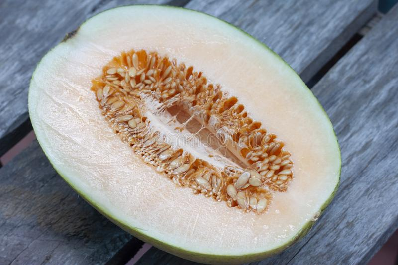Sliced half Cantaloupe on wooden table background. royalty free stock photography