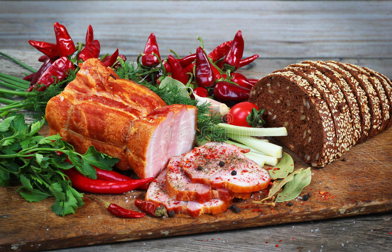 Sliced ham and bread with green and red vegetables on chopping b. Oard stock image