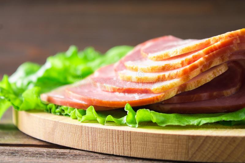 Sliced ham with fresh green lettuce leaves on a round cutting board. Meat products on a brown wooden table. royalty free stock photos