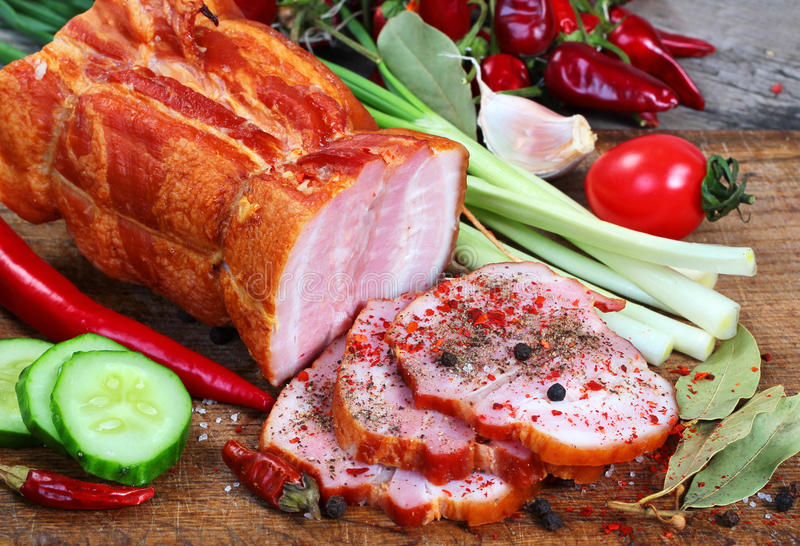 Sliced ham with green and red vegetables on chopping board.  stock image