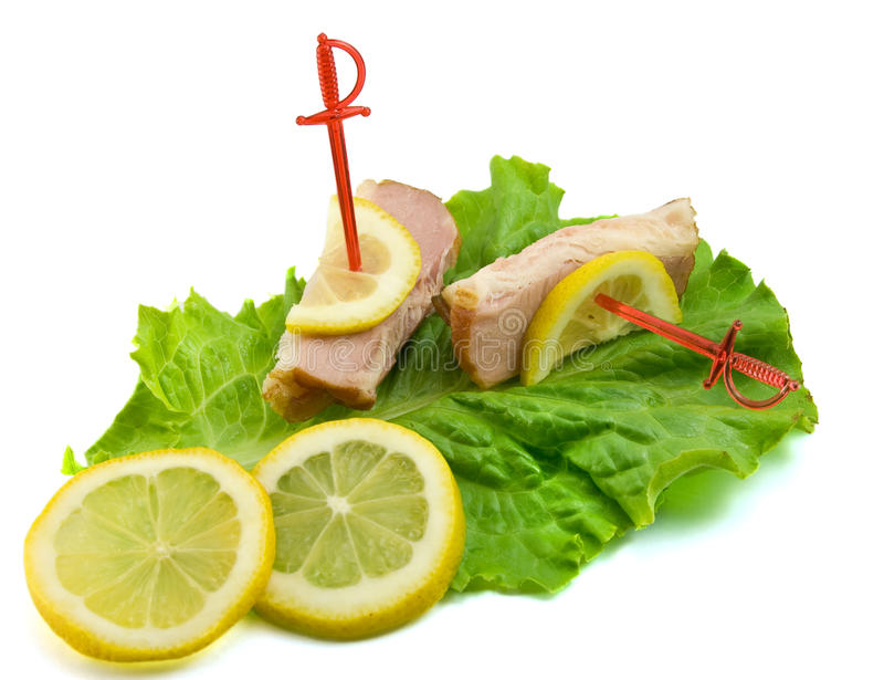 Sliced ham on leaves of salad with lemon