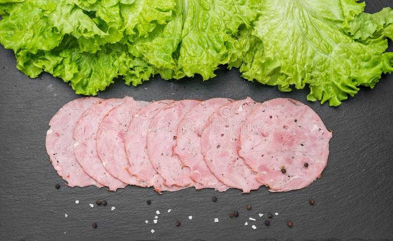 Sliced ham sausage on a stone background stock photography