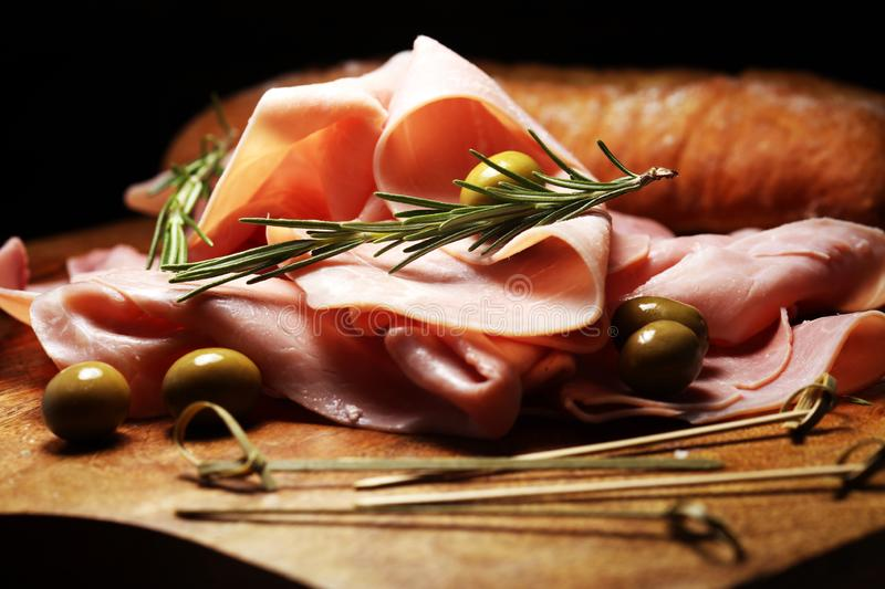 Sliced ham on wooden background. Fresh prosciutto cotto. Pork ham sliced with herbs royalty free stock image
