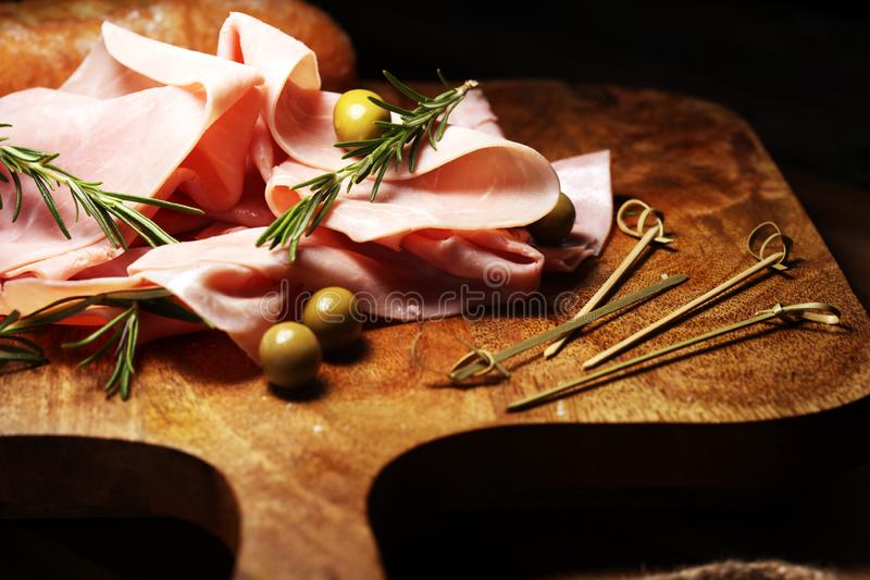 Sliced ham on wooden background. Fresh prosciutto cotto. Pork ham sliced with herbs stock images
