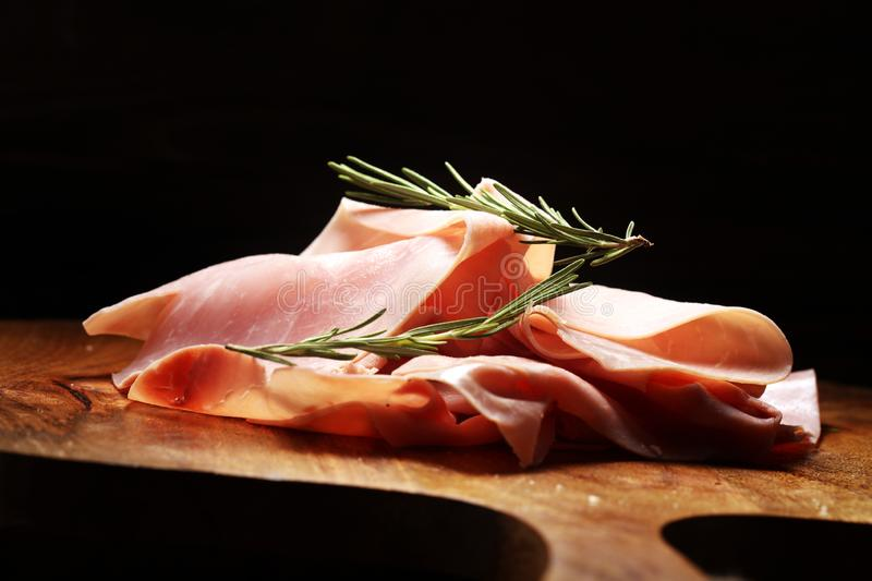 Sliced ham on wooden background. Fresh prosciutto cotto. Pork ham sliced with herbs royalty free stock images