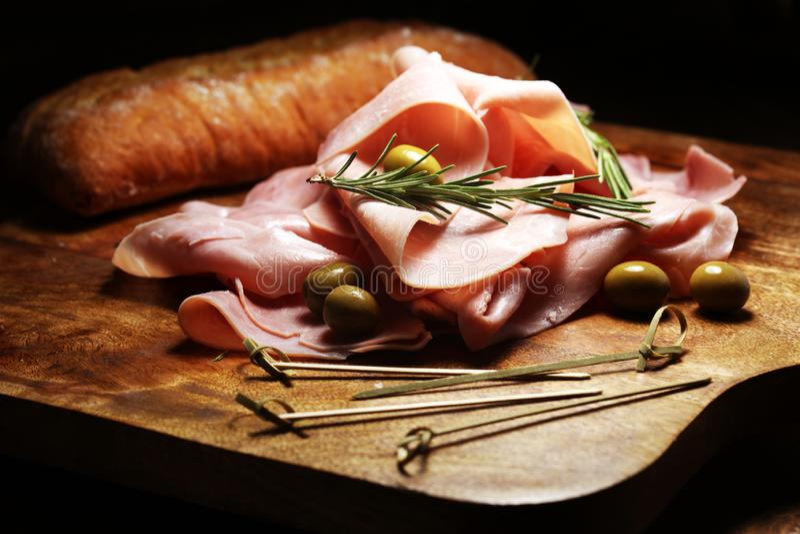 Sliced ham on wooden background. Fresh prosciutto cotto. Pork ham sliced with herbs stock photo