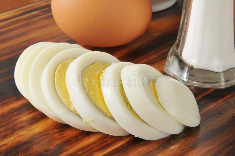 Sliced hard boiled egg. A sliced hard boiled egg with a shaker of salt stock images