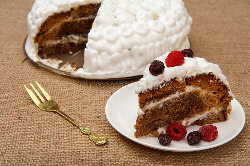 Sliced homemade biscuit cake decorated with whipped cream on plates royalty free stock images