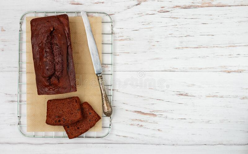 Sliced homemade chocolate banana pound cake loaf. Delicious dessert for Breakfast. A treat for tea. Ingredients on a light wooden table. Selective focus, copy royalty free stock photography