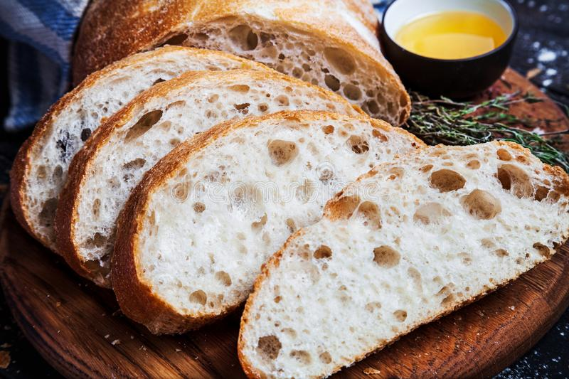 Sliced homemade italian ciabatta bread with olive oil on dark background. Ciabatta, herbs, olive oil, flour. Close up view, copy s stock photography