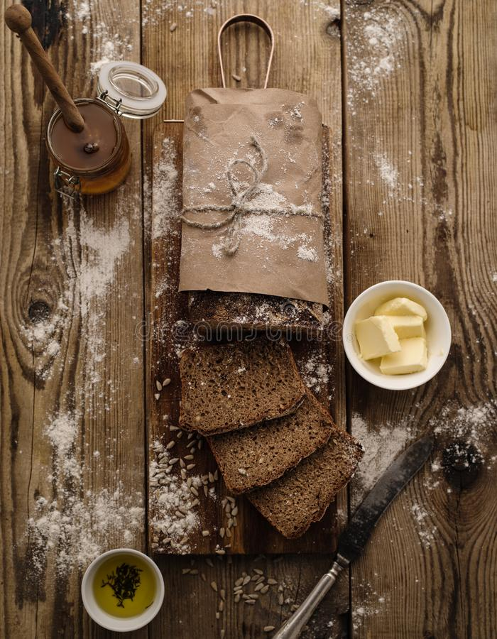 Sliced homemade rye bread on a wooden background with butter and stock photography