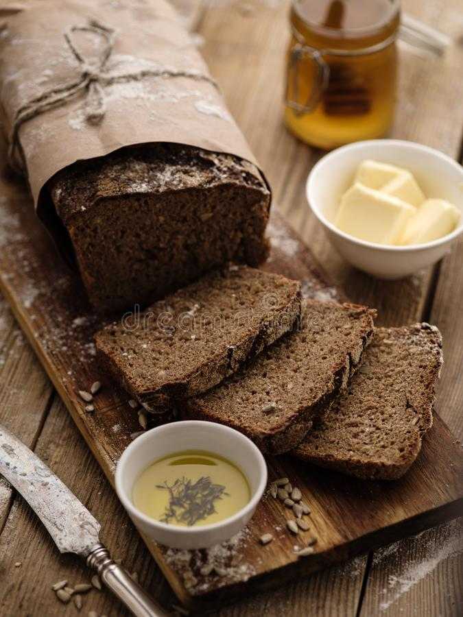 Sliced homemade rye bread on a wooden background with butter and royalty free stock photography