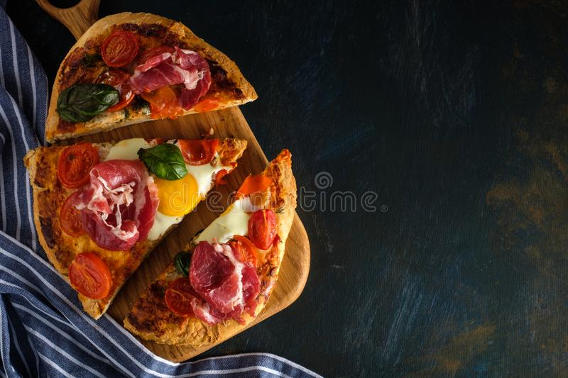 Sliced Homemade tasty pizza with bacon, egg, cheese, tomatoes an stock photos