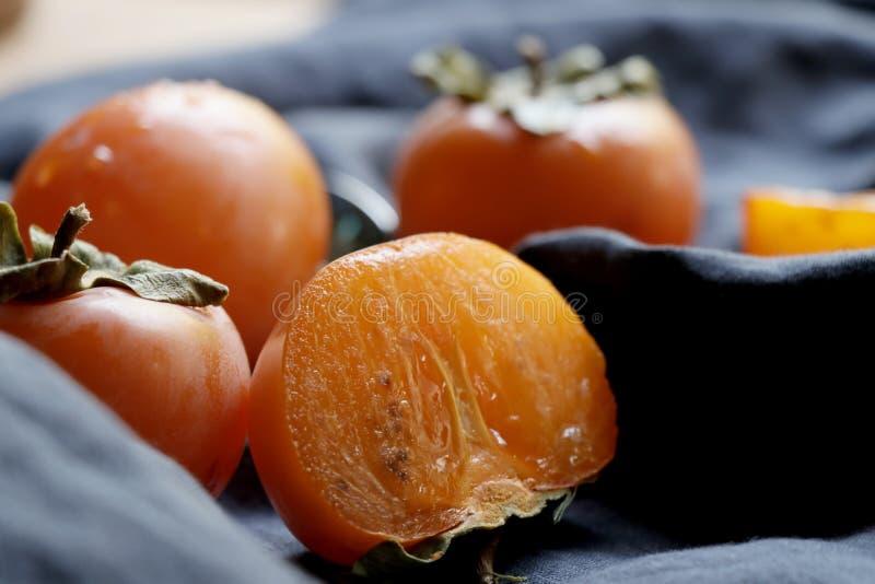 Sliced kaki on basket.Ripe orange persimmon fruit. royalty free stock photo