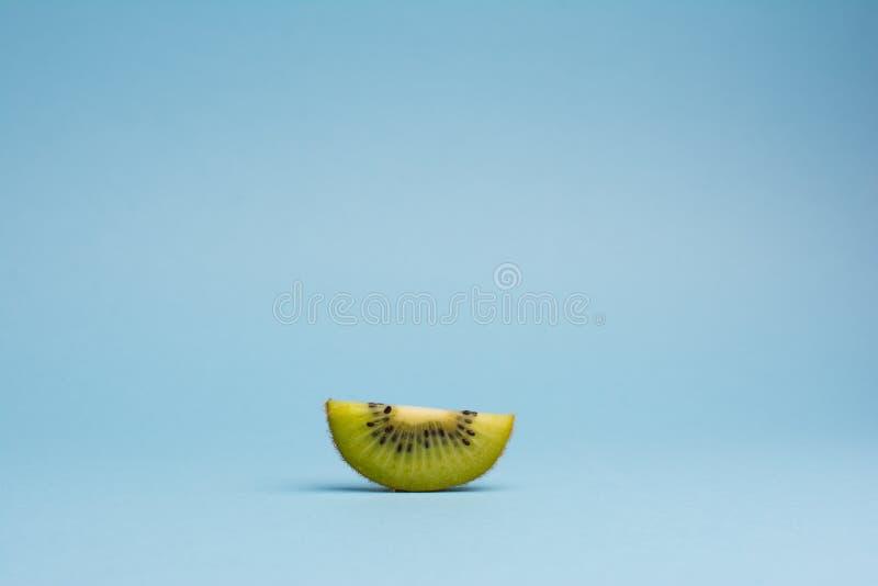 Sliced kiwi fruit on blue background stock photography