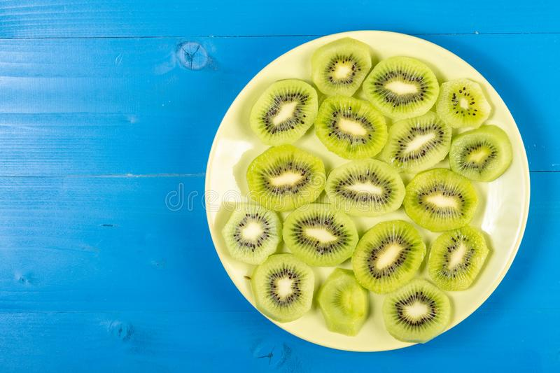 Sliced Kiwi Fruit On The Plate With Blue Table Background stock photo