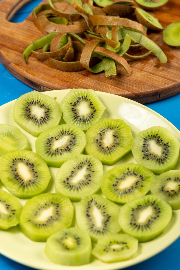 Sliced Kiwi Fruit On The Plate and Wooden Cutting Board royalty free stock photo
