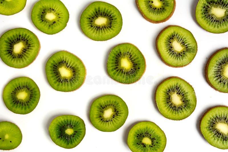 Sliced kiwi fruit on white background pattern. Sliced kiwi fruit on white background making a pattern isolated flat lay kiwifruit top green organic mix exotic royalty free stock photography