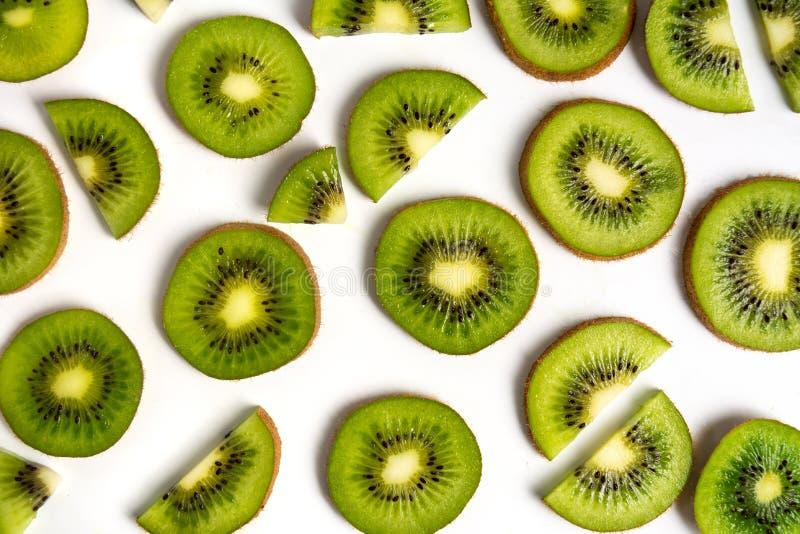 Sliced kiwi fruit on white background pattern. Sliced kiwi fruit on white background making a pattern isolated flat lay kiwifruit top green organic mix exotic stock photo