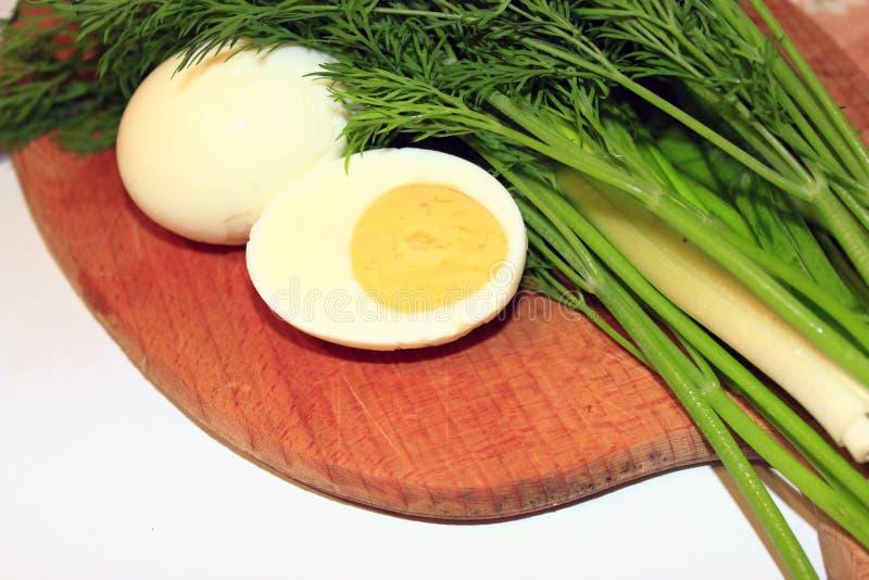 Sliced kokade ägget, salladslökar och dill arkivbilder