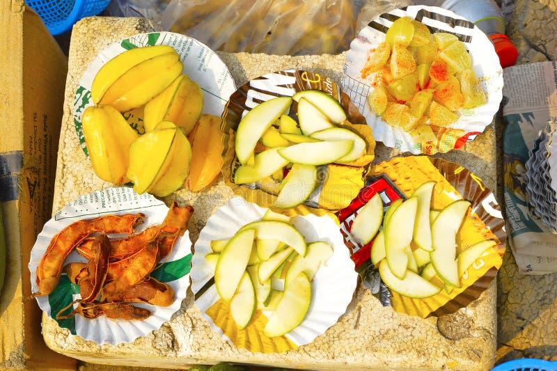 Sliced Konkani fruit like tamarind, amla or Indian gooseberry, raw mango and Star Fruit or Carambola for sale at Nagaon beach. Maharashtra, India royalty free stock images