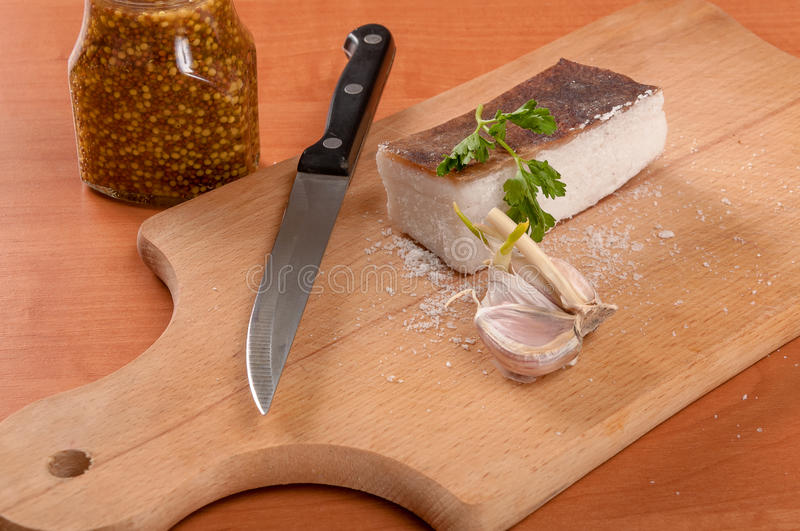 Sliced lard on wooden table with onion and knife horizontal royalty free stock photos