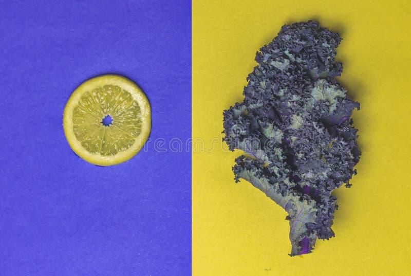 Sliced Lemon on Blue and Kale on Yellow. Single Sliced Lemon on Textured Blue Kale on Yellow stock photo