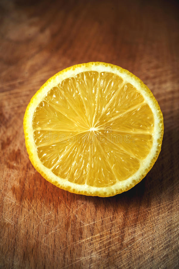 Sliced lemon on a cutting board .wooden background royalty free stock photography