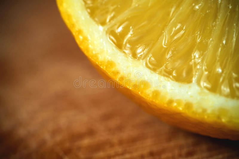 Sliced lemon on a cutting board .wooden background royalty free stock images