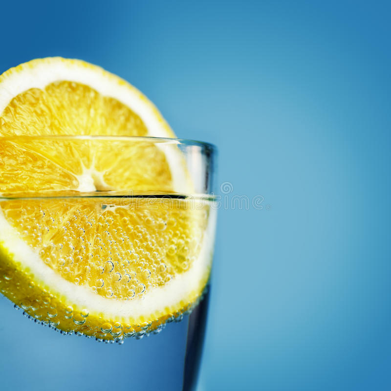 Sliced lemon in glass of water. Close-up with shallow depth of field royalty free stock image