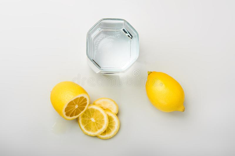 Sliced lemon with glass of water on the table royalty free stock photos