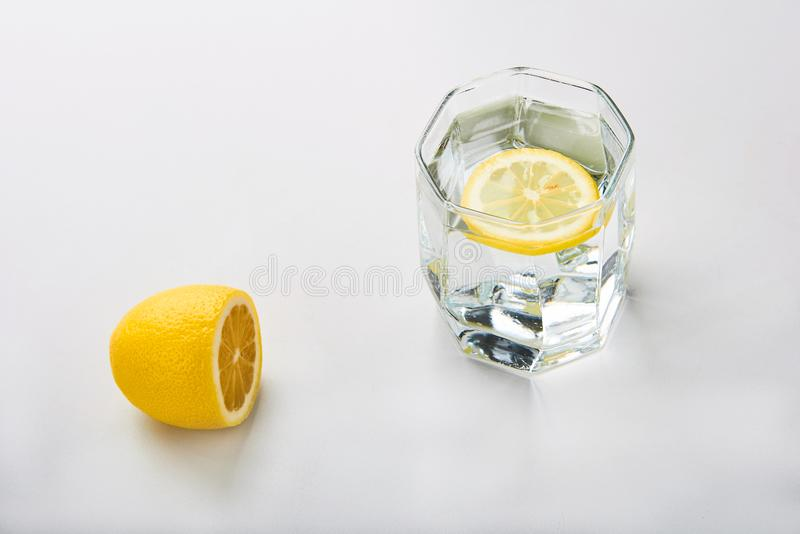 Sliced lemon with glass of water on the table royalty free stock image