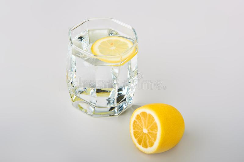 Sliced lemon with glass of water on the table royalty free stock photo