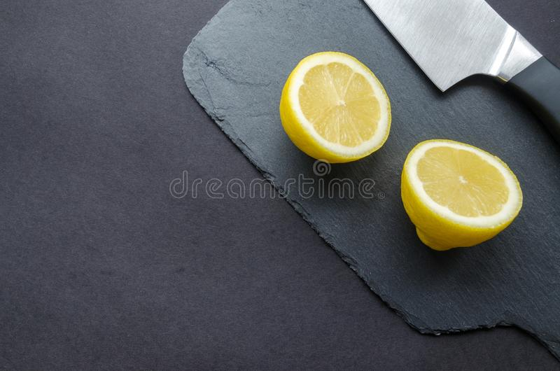 Sliced Lemon Beside Knife on Top of Black Surface stock image