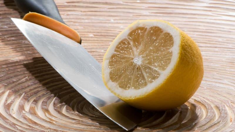Sliced lemon with knife stock image