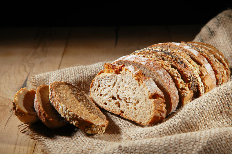 Sliced loaf of assorted rye bread on hessian. Sliced loaf composed of assorted crusty and seed covered rye bread on rustic hessian material showing the texture stock photo