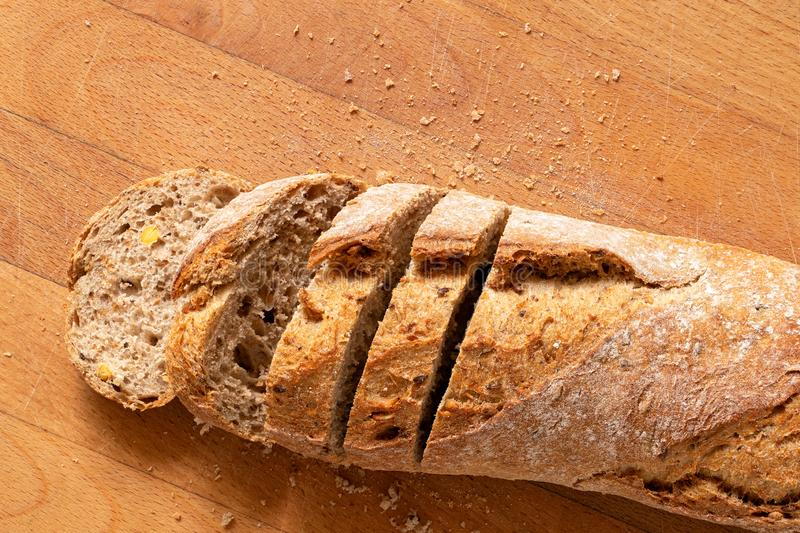 Sliced loaf of whole wheat european bread on light wood. Top view. Space for text stock images