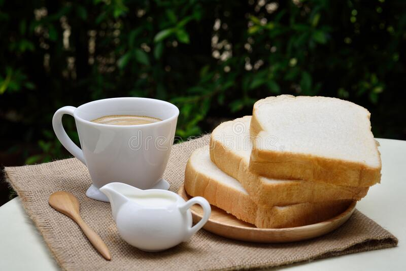 3 Sliced Loafs Beside White Ceramic Coffee Cup stock image