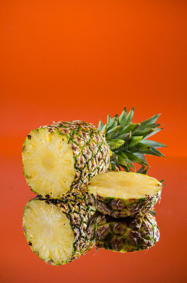 Sliced, lying pineapple on orange background, vertical shot. Picture presents sliced, lying pineapple on orange background, vertical shot royalty free stock images
