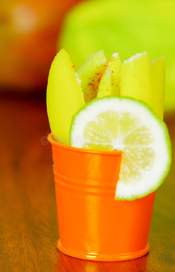 Sliced mango served with lemon on a plastic cup royalty free stock image