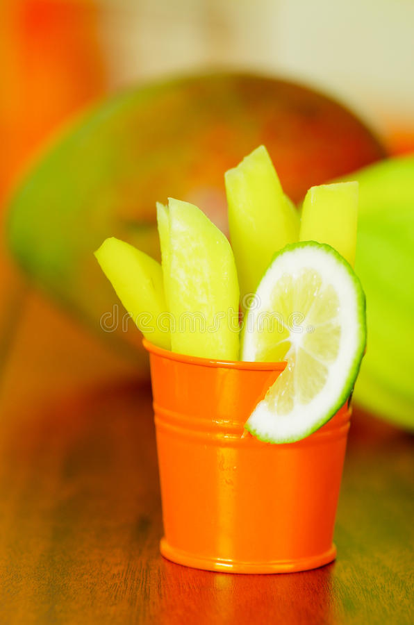 Sliced mango served with lemon on a plastic cup royalty free stock photography