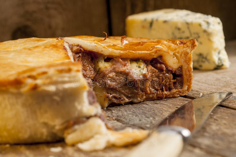 Sliced Meat Pie with Knife and Blue Cheese stock images