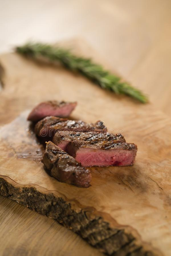 Sliced medium filet mignon on wood board. M shallow focus royalty free stock photos